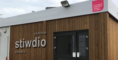Photographed: A wooden-clad building with 'Startup Stiwdio Sefydlu' and University of South Wales logo.
